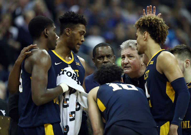 Head coach Bob Huggins of the West Virginia Mountaineers talks with players during a timeout