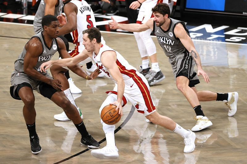 Goran Dragic #7 of the Miami Heat dribbles the ball against Reggie Perry #0 of the Brooklyn Nets and Joe Harris #12