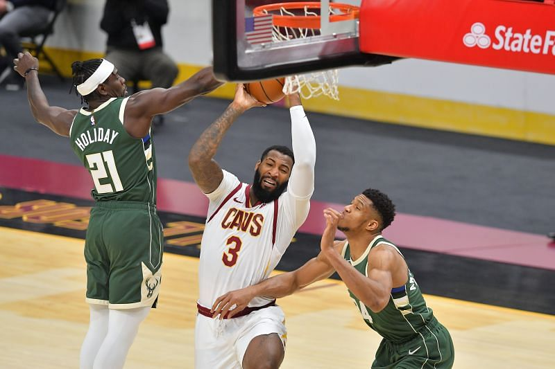 Andre Drummond #3 of the Cleveland Cavaliers drives to the basket while under pressure from Jrue Holiday #21 and Giannis Antetokounmpo #34 of the Milwaukee Bucks at Rocket Mortgage Fieldhouse (Photo by Jason Miller/Getty Images)