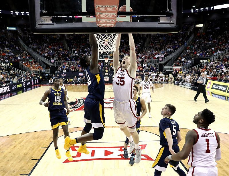 Brady Manek #35 of the Oklahoma Sooners dunks as Andrew Gordon #12 of the West Virginia Mountaineers defends