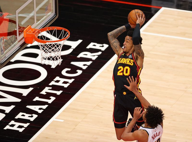 John Collins #20 of the Atlanta Hawks catches an alley-oop for a dunk against Zeke Nnaji #22 of the Denver Nuggets during the first half at State Farm Arena on February 21, 2021 in Atlanta, Georgia. (Photo by Kevin C. Cox/Getty Images)