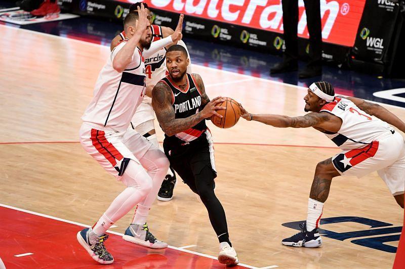 Damian Lillard of the Portland Trail Blazers goes up against Bradley Beal of the Washington Wizards
