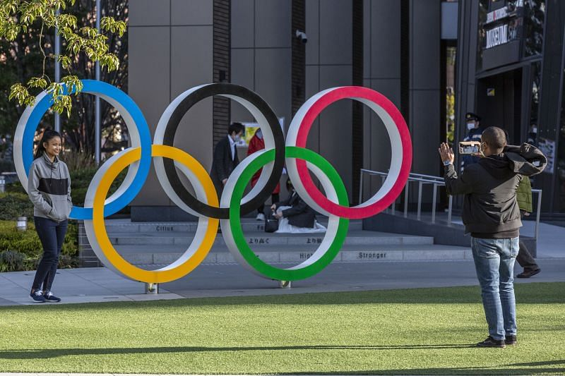 A woman has her photograph taken in front of the Olympic Rings in February 2021 in Tokyo, Japan.