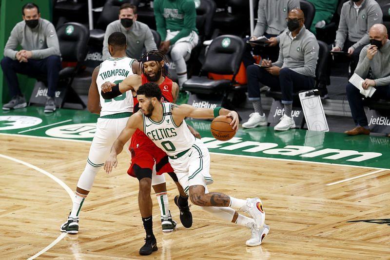 Jayson Tatum #0 drives towards the basket past DeAndre