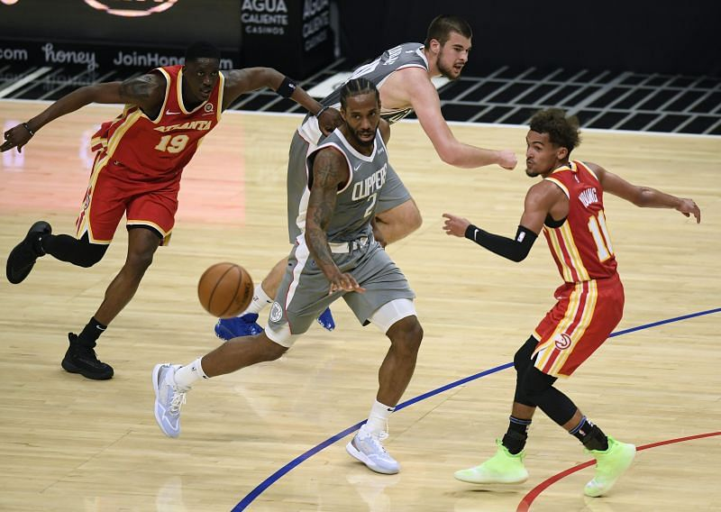 Kawhi Leonard (#2) passes between Trae Young (#11) and Tony Snell (#19)
