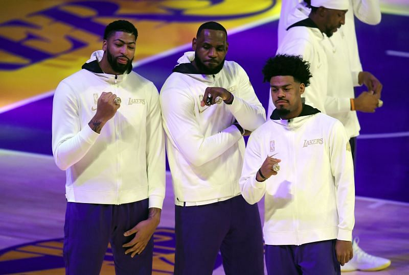 Anthony Davis #3, LeBron James #23, and Quinn Cook #2 of the Los Angeles Lakers pose during the 2020 NBA championship ring ceremony
