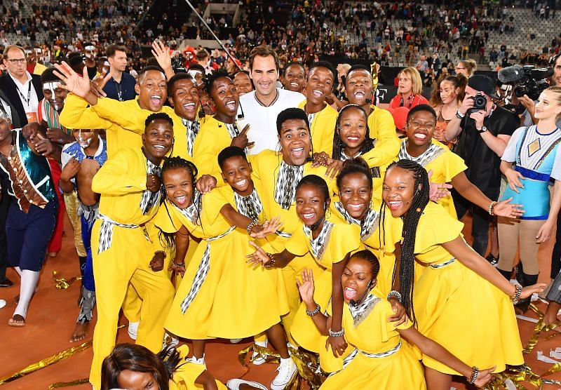 Roger Federer poses with kids at the Match In Africa 2020