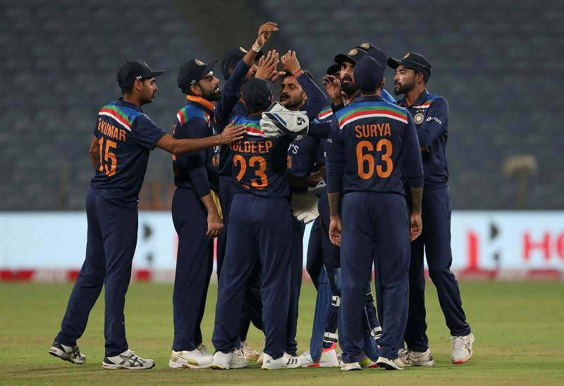 The Indian cricket team celebrating the fall of a wicket.