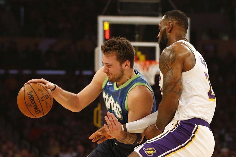 Luka Doncic (#77) of the Dallas Mavericks drives around LeBron James (#23) of the LA Lakers.