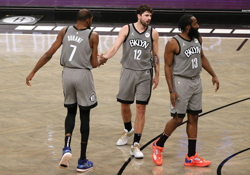 Kevin Durant #7 high fives Joe Harris #12 as James Harden #13 of the Brooklyn Nets looks on