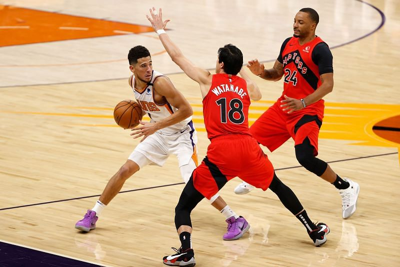 Devin Booker of the Phoenix Suns in NBA action against Yuta Watanabe of the Toronto Raptors