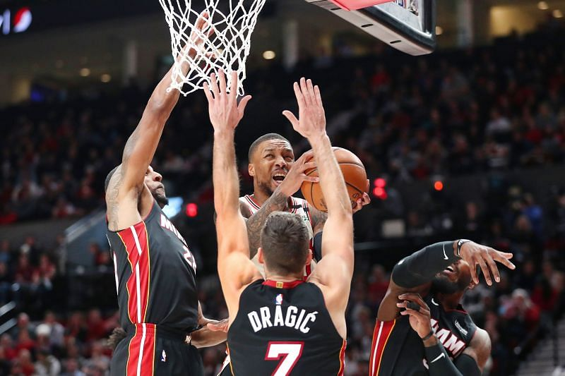 Damian Lillard #0 takes a shot against three players (Photo by Abbie Parr/Getty Images)