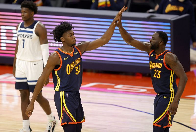 James Wiseman (L) celebrates with teammate Draymond Green during a match