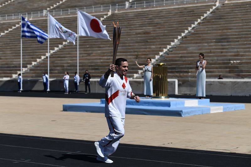 An athlete carries the Olympic Torch during the Flame Handover Ceremony for the Tokyo 2020 Summer Olympics in March 2020, in Athens, Greece