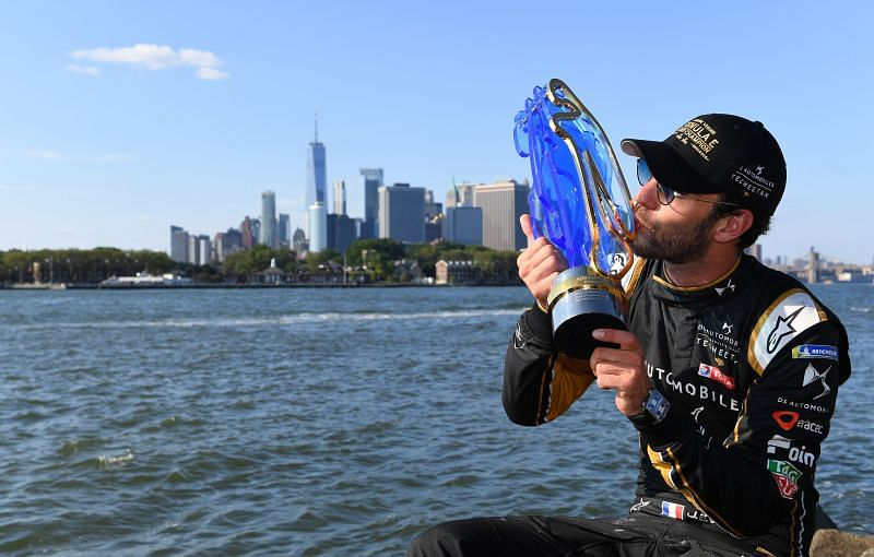 With the Manhattan skyline in the background, Jean-Eric Vergne kisses his championship trophy after the New York E-Prix. {Photo by FIA ABB Formula-E Handout/Getty Images,)