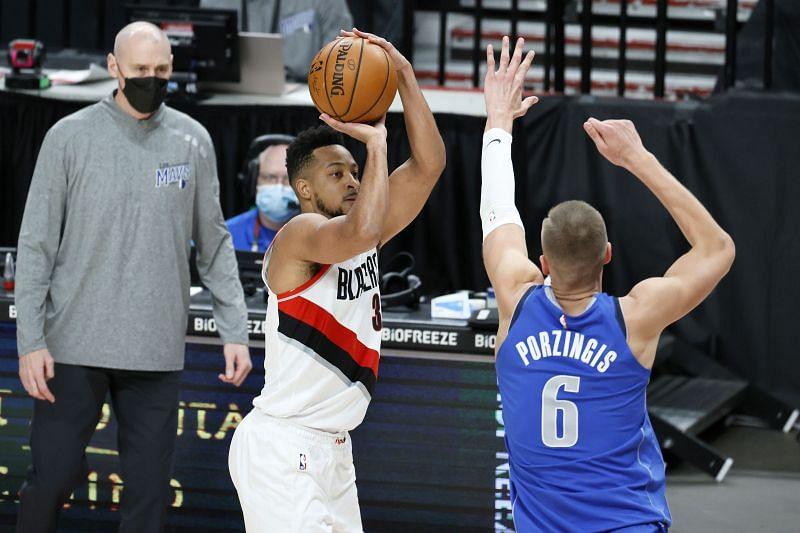 CJ McCollum of the Portland Trail Blazers shoots over Kristaps Porzingis of the Dallas Mavericks