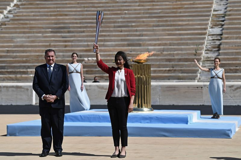 Greek Sports Minister and HOC President, Spyros Capralos hands over the Olympic torch to former Japanese swimmer Imoto Naoko during the Flame Handover Ceremony for the Tokyo 2020 Summer Olympics in March 2020, in Athens, Greece