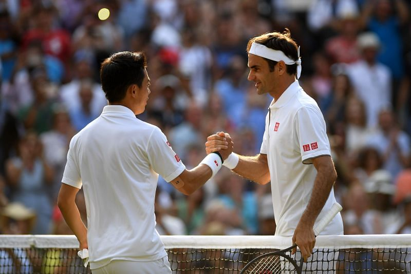 Roger Federer shakes hands with Kei Nishikori at Wimbledon 2019