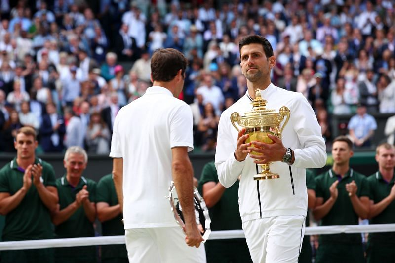 Novak Djokovic walks past Roger Federer with the Wimbledon 2019 title
