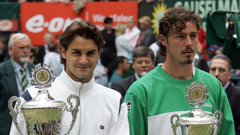 Roger Federer and Marat Safin (R) pose at the 2005 Halle Open trophy ceremony