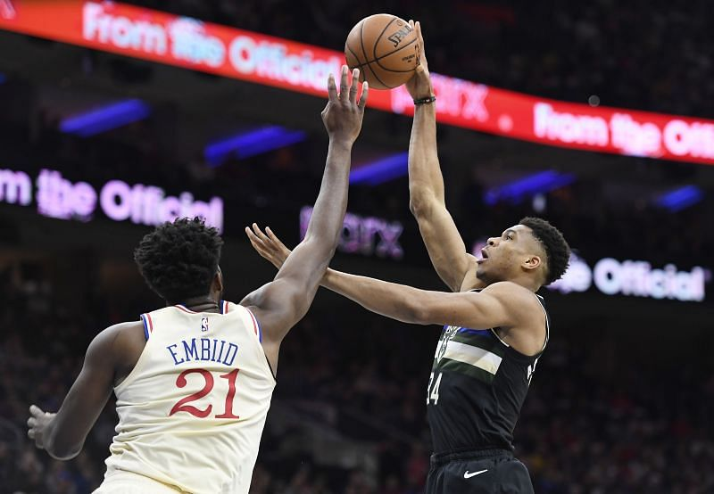 Giannis Antetokounmpo #34 of the Milwaukee Bucks attempts a shot as Joel Embiid #21 of the Philadelphia 76ers defends.