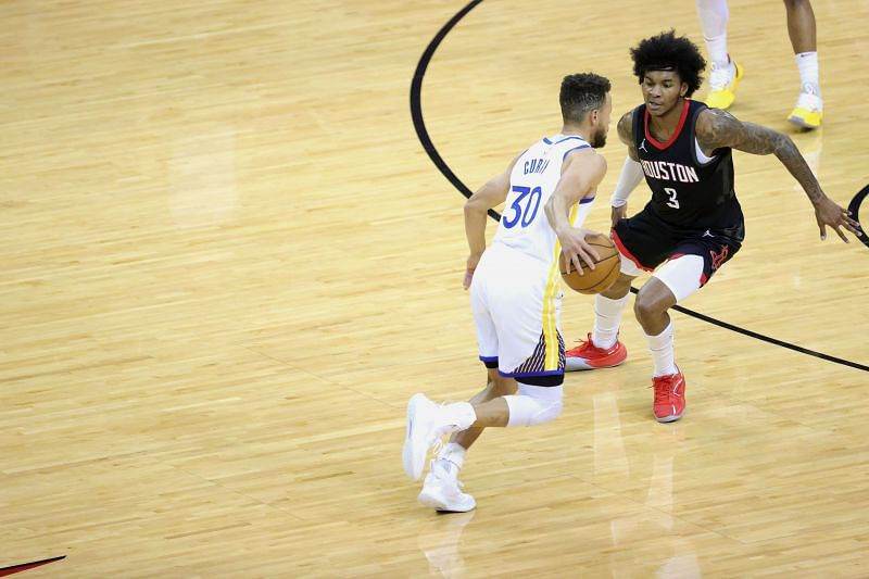 Stephen Curry (#30) controls the ball against Kevin Porter Jr. (#3).