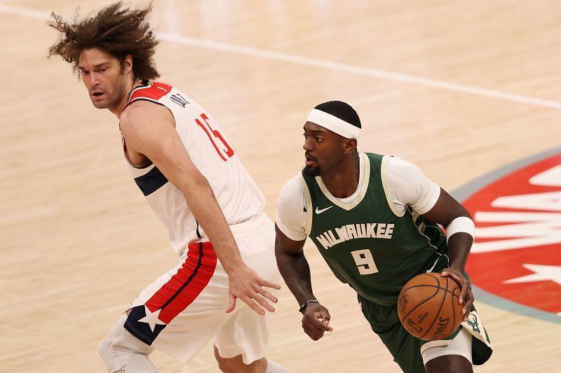 Bobby Portis #9 of the Milwaukee Bucks dribbles past Robin Lopez #15 of the Washington Wizards.