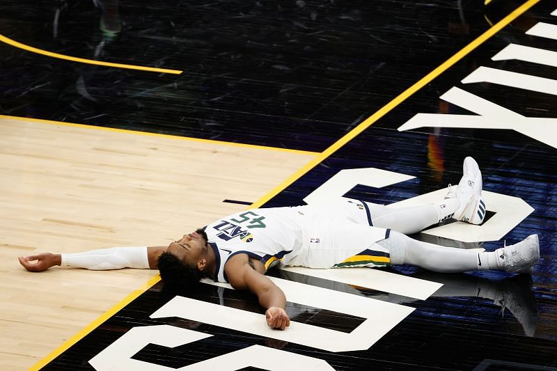 Donovan Mitchell #45 lays on the court after scoring and drawing a foul.