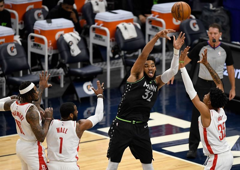 Karl-Anthony Towns #32 passes the ball away from three Houston Rockets players