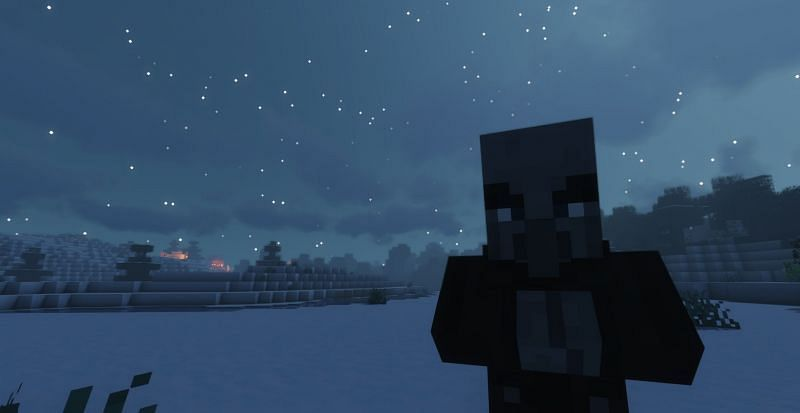 Shown: A Vindicator plotting the destruction of the village in the background (Image via Minecraft)