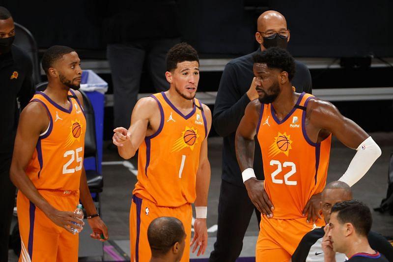 Phoenix Suns star Devin Booker with teammates Mikal Bridges and Deandre Ayton.