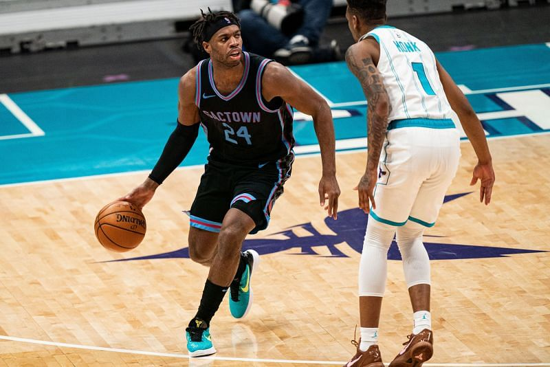 Buddy Hield #24 brings the ball up court while being guarded by Malik Monk #1