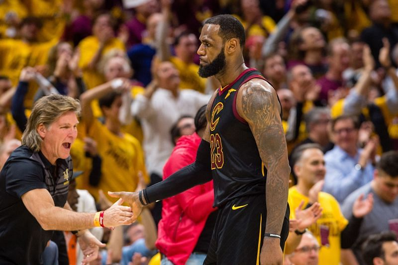 LeBron James #23 of the Cleveland Cavaliers celebrates with a fan after scoring against the Toronto Raptors.