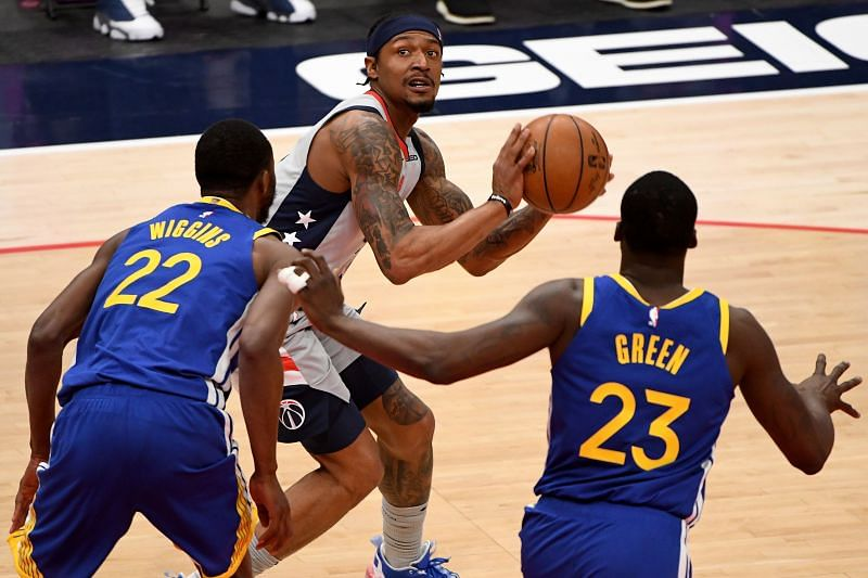 Andrew Wiggins and Draymond Green of the Golden State Warriors guarding Bradley Beal
