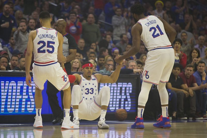 Ben Simmons #25 and Joel Embiid #21 help Tobias Harris #33 off the floor