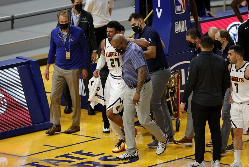 Jamal Murray #27 of the Denver Nuggets is helped off the court after an injury in their game against the Golden State Warriors.