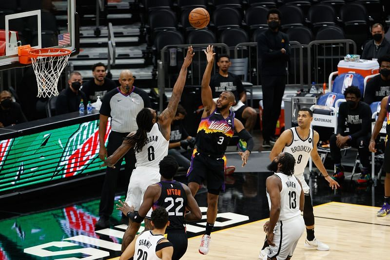Chris Paul, #3 of the Phoenix Suns, puts up a shot over DeAndre Jordan #6 of the Brooklyn Nets.