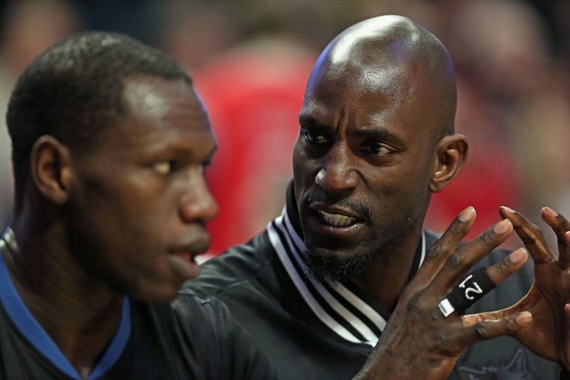 Kevin Garnett (right) talks with teammate Gorgui Dieng (#5) on the bench.