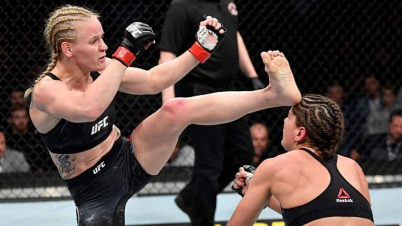 Valentina Shevchenko (left) head kicks Jessica Eye (right) at UFC 238.