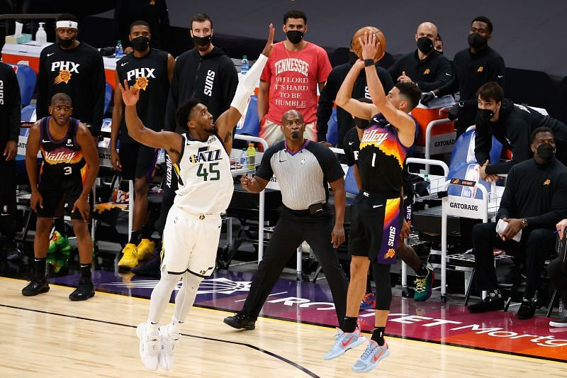 Booker #1 of the Phoenix Suns attempts a three-point shot over Donovan Mitchell #45 of the Utah Jazz