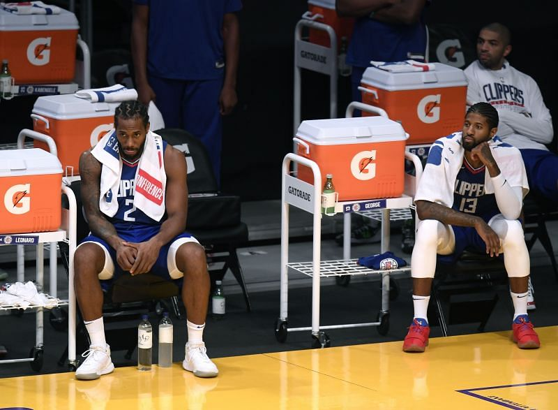 Kawhi Leonard #2 and Paul George #13 watch a game from the bench