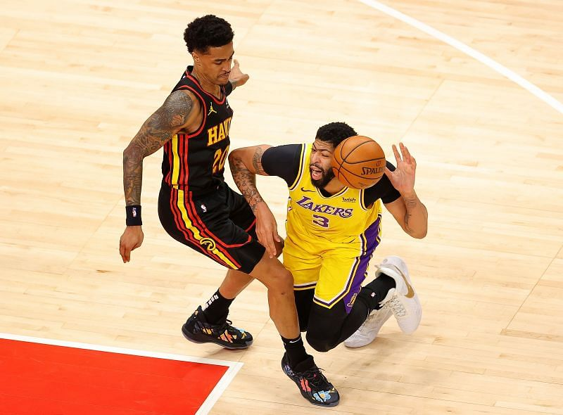 Anthony Davis #3 draws a foul as he falls the court against John Collins #20.