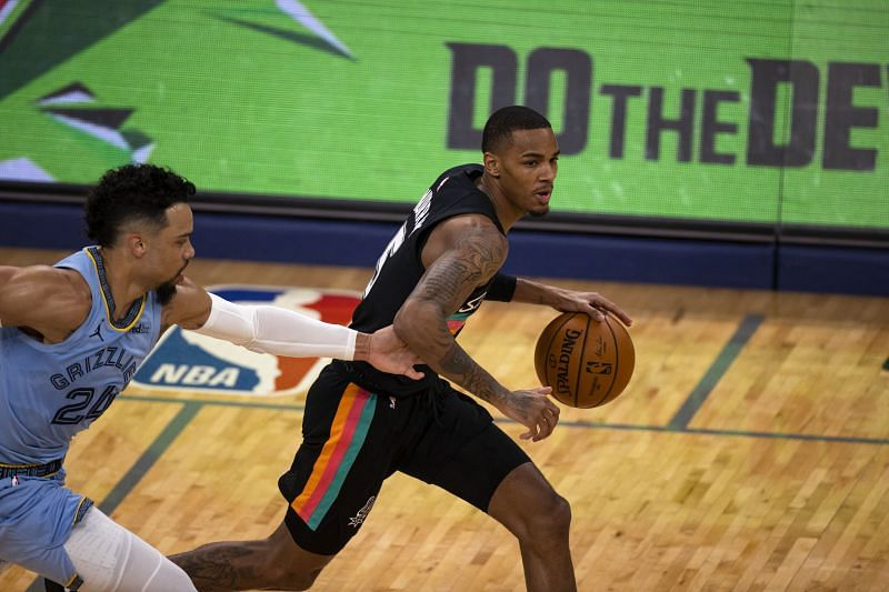 Dejounte Murray (#5) dribbles the ball up the court as Dillon Brooks (#24) reaches to defend.