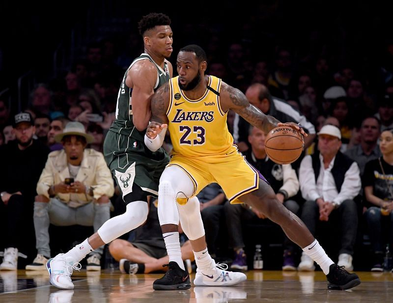 LeBron James #23 of the Los Angeles Lakers backs in on Giannis Antetokounmpo #34 of the Milwaukee Bucks