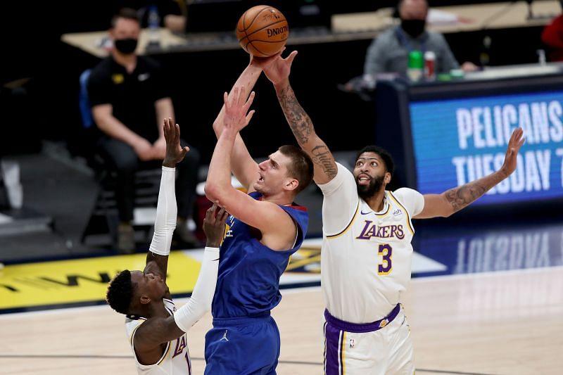 Nikola Jokic #15 goes to the basket against Dennis Schroder #17 and Anthony Davis #3.