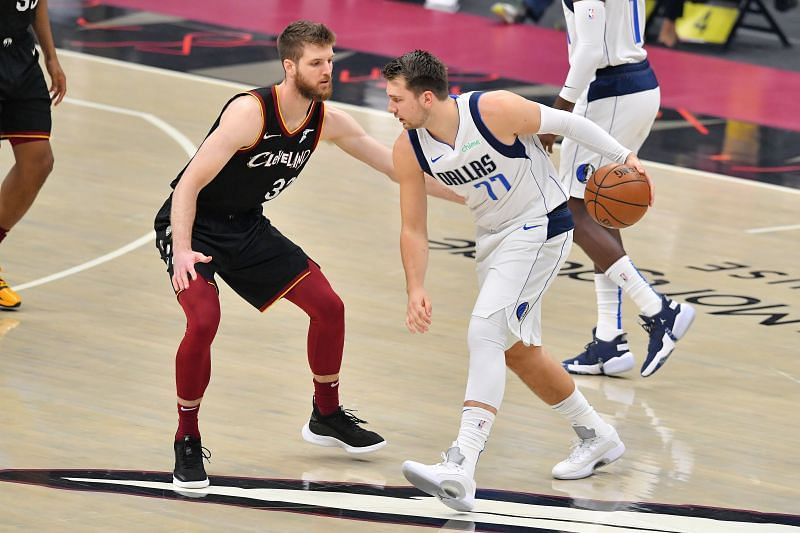 Luka Doncic #77 drives to the basket around Dean Wade #32