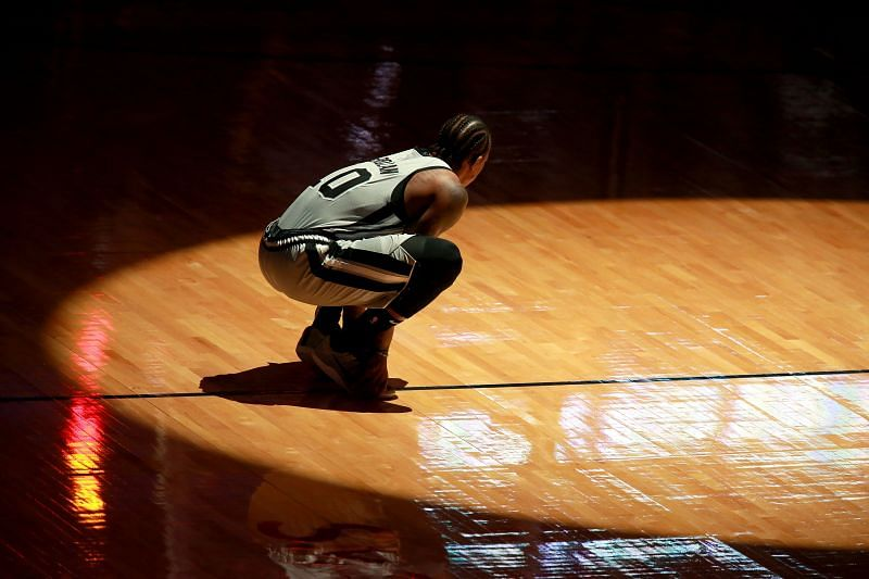 DeMar DeRozan #10 of the San Antonio Spurs kneels on the court prior to the start of an NBA game
