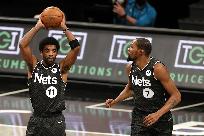 Kyrie Irving #11 looks to pass as Kevin Durant #7 looks on during a first half game