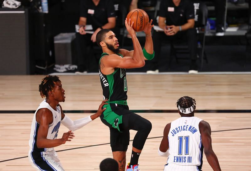 Jayson Tatum #0 of the Boston Celtics shoots against Wes Iwundu #25 and James Ennis III #11 of the Orlando Magic.