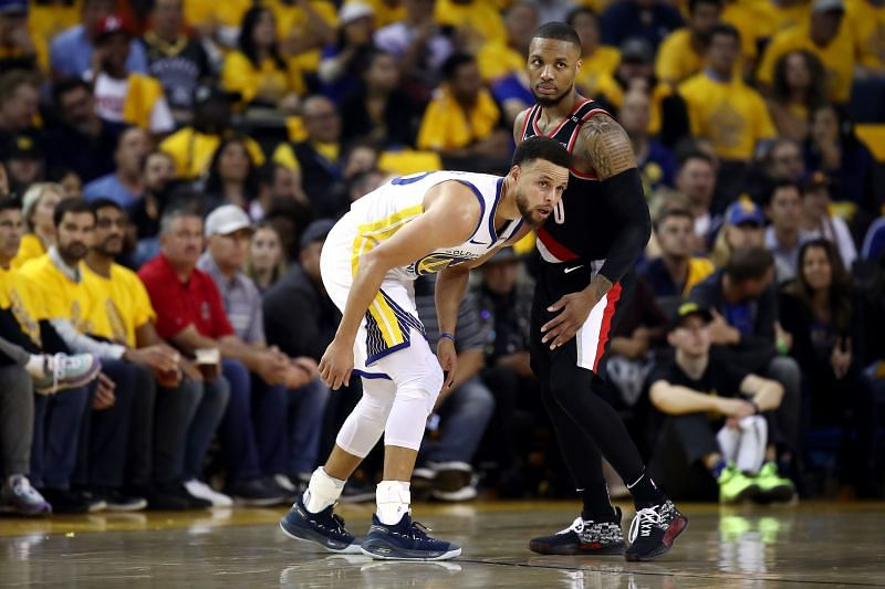 Stephen Curry #30 and Damian Lillard #0 look on during the second half.